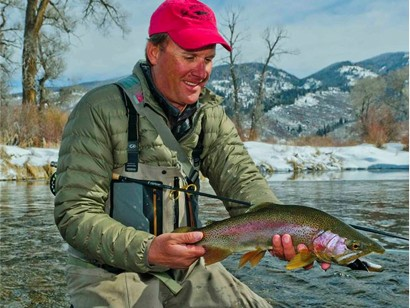 Pat Dorsey holding Large Trout above river with winter mountains in the background