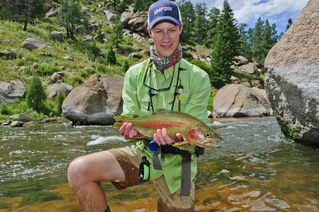 Closeup of man holding a large trout in the tailwaters at Cheesman Canyon